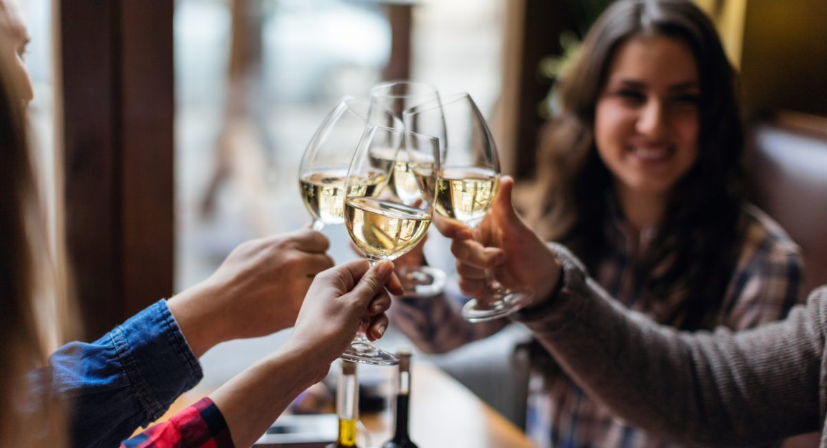 Friends toasting each other with white wine, smiling, sitting in restaurant